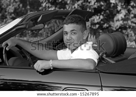A young man getting ready to go for a ride in his convertible.
