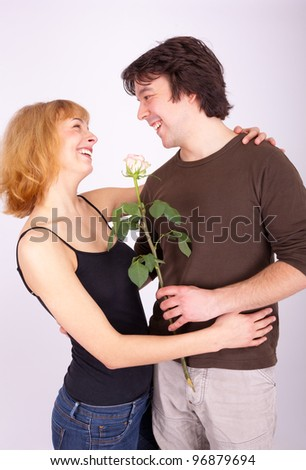 A young man gives his girlfriend a rose