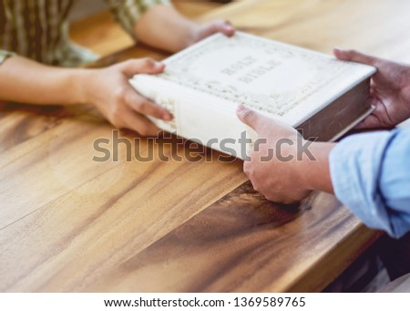 A young man giving big old book of holy bible to his friend on wood table in working place. Christian background,  share the world of God or gospel concept with copy space. #1369589765