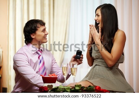 A young man giving engagement ring to his girlfriend while making her proposal