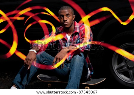 A young man hanging out seated on his skateboard with abstract light trails glowing around him and through his fingers.