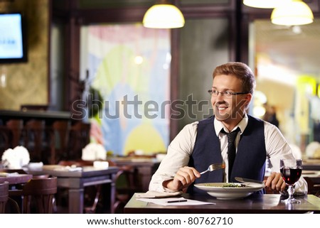 A young man having dinner in a restaurant