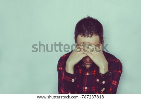 A young man hides his eyes with his hands. Sad man sitting covering his face. The guy sitting alone and going through. The concept of depression and grief. Unrequited love.
