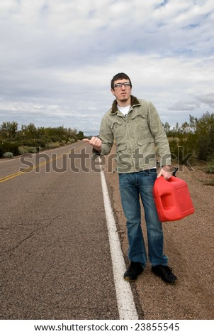 A young man hitchikes to catch a ride for some gasoline.