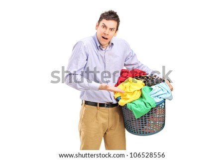 A young man holding a laundry basket and gesturing isolated on white background