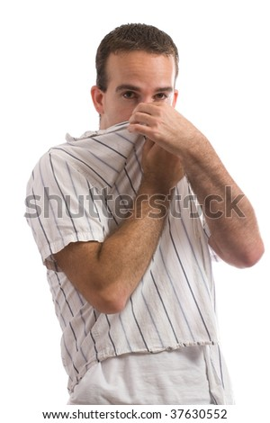 A young man holding his nose because of a bad smell, isolated against a white background