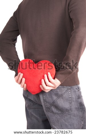 A young man holds a heart shaped pillow behind his back which he gives as a present to his girlfriend for valentines day. Isolated over white.