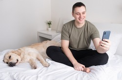 A young man holds a mobile phone while sitting on a bed with a dog and caresses his pet. Portrait of male owner spending time at home in bedroom scratching golden retriever.