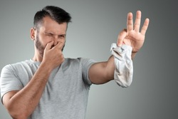 A young man holds his smelly socks and covers his nose with his hand. Nasty smell. Stink legs, fungus on the legs.