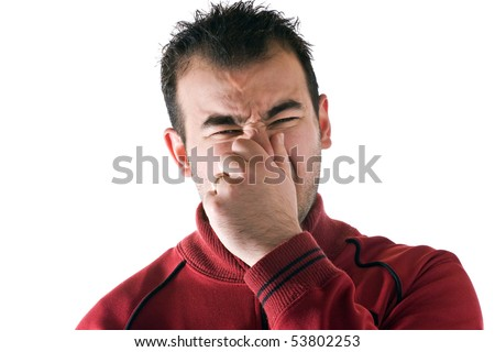 A young man holds or pinches his nose shut because of a stinky smell or odor. - stock photo