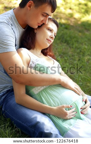 A young man hugging his pregnant happy wife,outdoor
