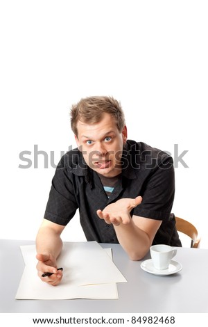 A young man in a black shirt sitting at a table and vigorously talking to you posing in studio isolated on a white background