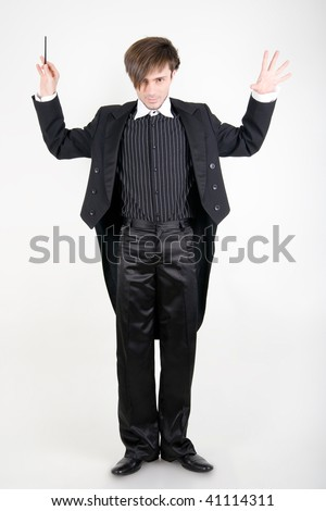 A young man in a black tailcoat with his hands up is looking from under the brows