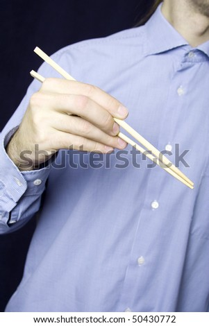 A young man in a blue shirt in his hand, wooden sticks for land - stock photo