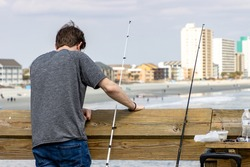A young man in a grey shirt and jeans peers over the side of the Garden City Pier while fishing near the ocean travel destination of Myrtle Beach, South Carolina, USA.