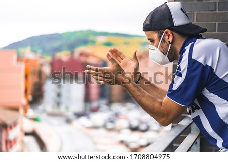A young man in a mask and a blue and white shirt applauding the toilets on the balcony at 8 in the afternoon. Pandemic coronavirus in Spain