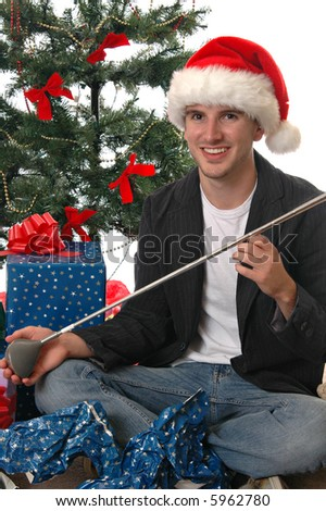 A young man in a Santa hat opening a golf club for Christmas - stock photo