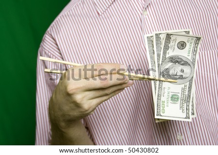 A young man in a striped shirt on a green background holding wooden chopsticks from Sushi hundred dollar bills