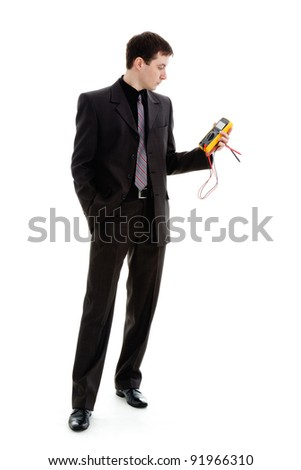 A young man in a suit, looks at the testimony of a multimeter, isolated on a white background.