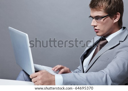 A young man in a suit with a laptop