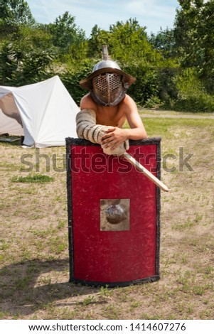 A young man in a vintage helmet and arm protection stands in the field, leaning on the battle square red shield at the festival of medieval battles. Knight's armor ready for combat gladiators battles