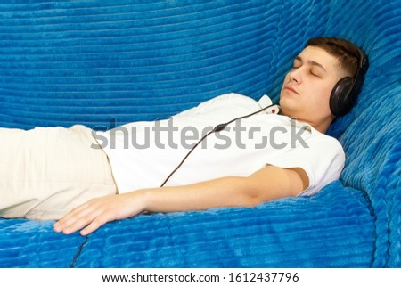 a young man in a white t-shirt at home listening to relaxing music. relaxation relaxation, calmness