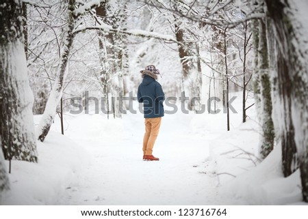 A young man in a winter forest, seen from behind