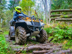 A young man in a yellow helmet rides through the woods on a Quad bike. Extreme hobby. A trip to ATV on the road from logs. Quad Biking through the forest. Rental of ATV.