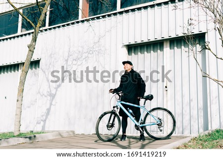 a young man in black sportswear holds a Bicycle standing next to him, against the background of a light hangar on a Sunny spring day