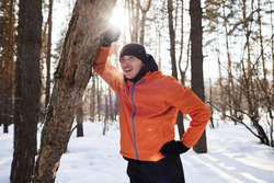 A young man in bright sports clothes enjoys a jog in the woods on a winter day