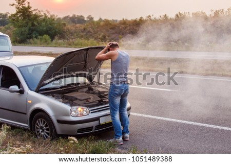 A young man in despair clutched his head, because his car broke down on the road and it is not possible to repair it. Smokes from under the hood. #1051489388