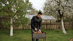 A young man in his prime cooks barbecue on the grill. He's outside. Barbecue stands on the green grass. In the background, trees blooming in spring