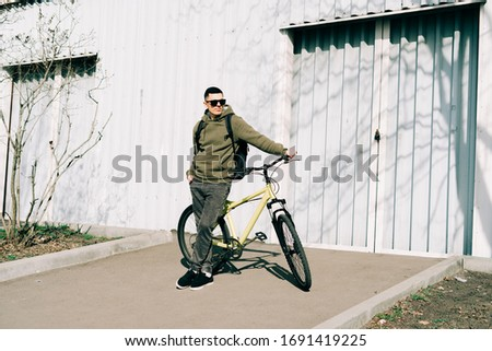 a young man in khaki sportswear holds a Bicycle standing next to him, against the background of a light hangar on a Sunny spring day
