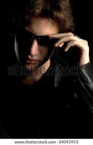 A young man in leather jacket and sunglasses, black background