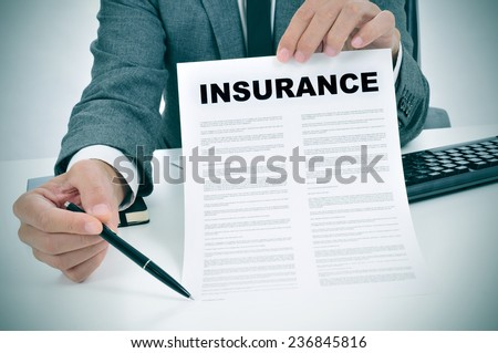 a young man in suit in his office showing an insurance policy and pointing with a pen where the policyholder must to sign Stock foto ©