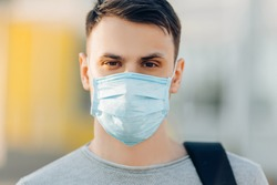 A young man in the background of an open- air building wearing a medical face mask that protects against the spread of coronavirus disease. Close- up of a man with a surgical mask on his face