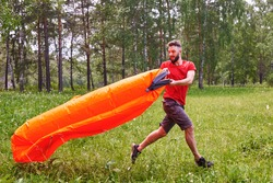 A young man inflates a lamzac with air. A man inflates an air sofa. on the background of the forest.