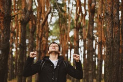 A young man inhales clean forest air on his full chest. Breath in breath out. Breathing exercises. Travel, ecotourism, ecology, local tourism, success concept, natural background.