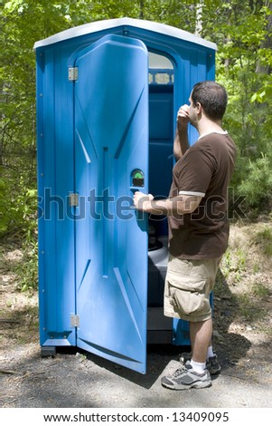 A young man investigating a blue porta potty located on the hiking trail.  Desperate times call for desperate measures.