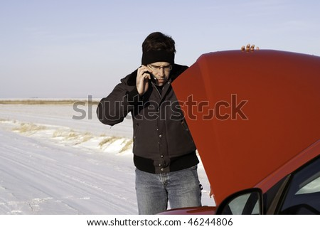 A young man is checking under the car hood while talking on a cell phone.