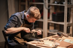 a young man is engaged in the family craft of making leather shoes in a workshop