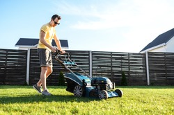 A young man is going to mow the lawn, he starts a push lawn mower. A guy in casual yellow t-shirt and in sunglasses