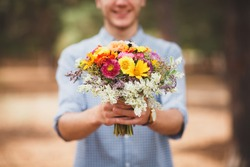 A young man is holding a beautiful bouquet of autumn flowers in his hand. The guy decided to make a surprise to his girlfriend. Romantic gift for the girl. Coniferous forest in autumn. background blur