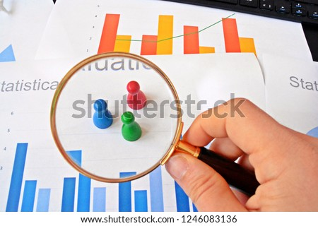 A young man is holding a magnifying glass in his hand, looking at statistic figures - a business concept on the subject of sampling and selecting the right target group and examining it #1246083136