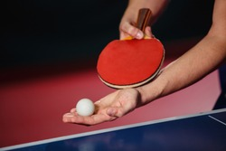 A young man is playing ping pong. He holds a ball and a racket in his hands