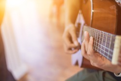 A young man is practicing playing guitar in a music practice room before performing in order to reduce the mistake of playing guitar on stage. Close Up Young man is holding guitar chords for practice.