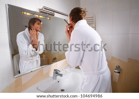 A young man is shaving his face in front of the bathroom mirror.