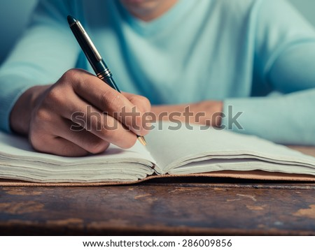 A young man is sitting at a table and is writing in a notebook