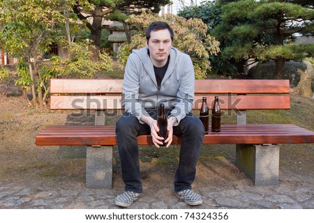 A young man is sitting on a bench drinking beer