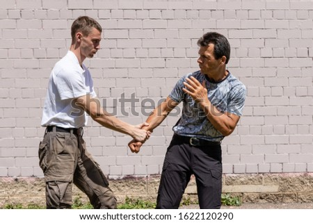A young man is trying to keep an opponent by grabbing his wrist. Martial arts instructors demonstrate self-defense techniques of Krav Maga